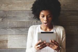 black student reading tablet