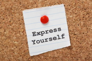 The words Express Yourself typed on a scrap of lined paper pinned to a cork notice board