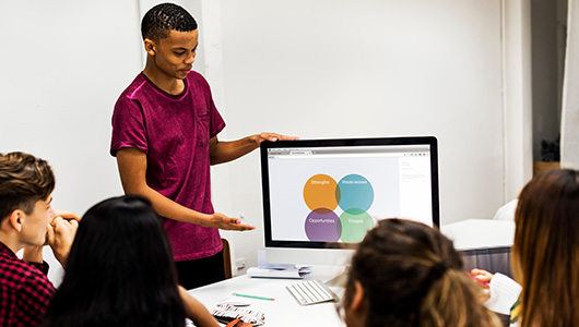 photo of student making a presentation on a laptop