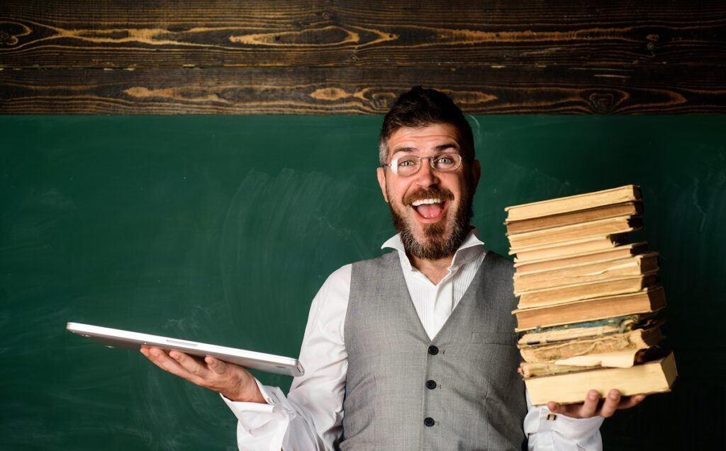 teacher with laptop and books