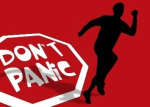 """A stop sign with text """"Don't panic"""" with a black outline of a person running away."""