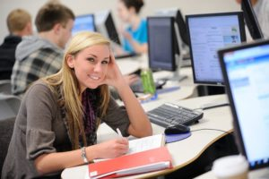 Student smiling sitting in a computer lab with other students.
