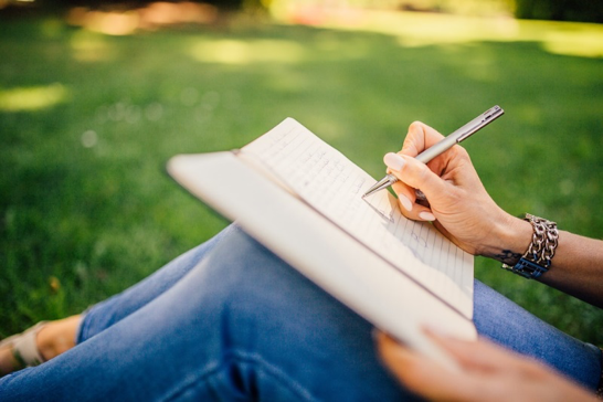 Image of book on a person knees while she is writing outdoors on a sunny day.