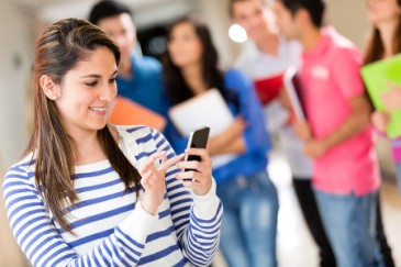 Student looking at her phone in school hallway with students holding notebooks behind her.