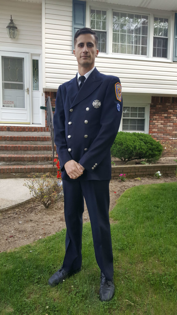 Student Michael Kelly in a suit, tie, and formal paramedic uniform outdoors in front of his house.