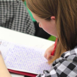 Female student writing on piece of paper while sitting at a desk.