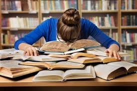 woman with head in books studying